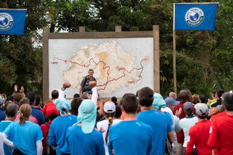 Bear Grylls standing in front of a custom topographic map made by East View Geospatial for World's Toughest Race: Eco Challenge Fiji